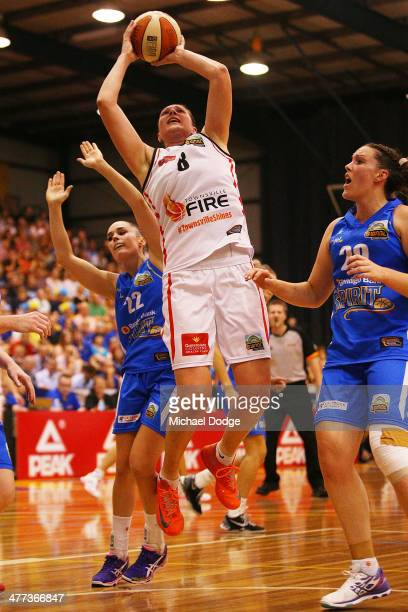 Suzy Batkovic of the Fire drives to the basket against Kelsey Griffin and Kelly Wilson of the Spirit during the WNBL Grand Final match between...
