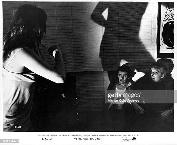 Suzy Kendall dances as Norman Rodway and Tony Beckley watch in a scene from the film 'The Penthouse' 1967