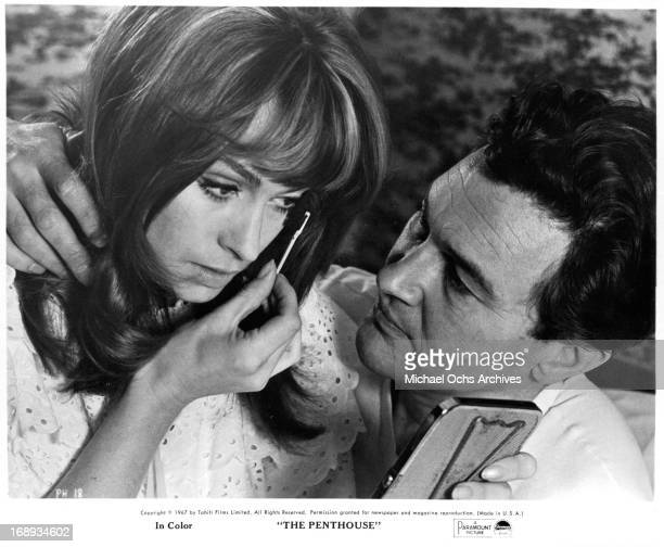 Suzy Kendall is putting on makeup while Terence Morgan watches in a scene from the film 'The Penthouse' 1967