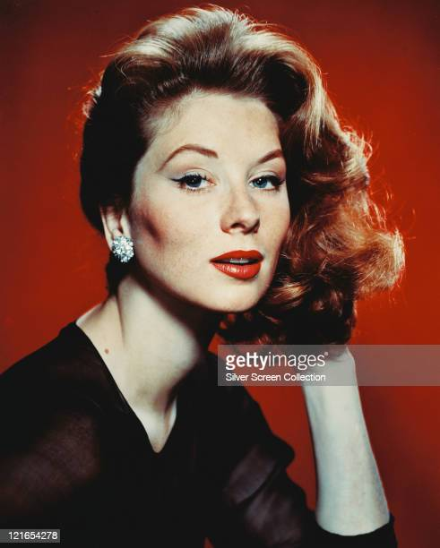 Suzy Parker US actress and model wearing a black chiffon top and diamond earrings in a studio portrait against a red beckground circa 1955