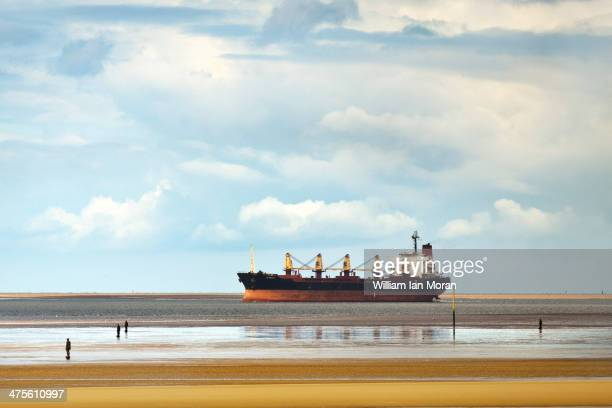 Sv Nikolay' a 22,000 tonne Panama registered cargo vessel enters the mouth of the river Mersey of Crosby beach with serveral of Anthony Gormleys...
