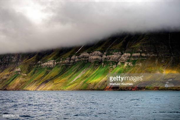 Svalbard rocky moss coastline and abandoned house