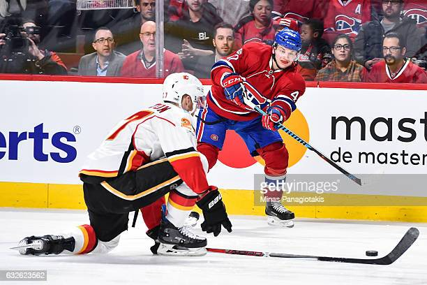 Sven Andrighetto of the Montreal Canadiens tries to play the puck past Dougie Hamilton of the Calgary Flames during the NHL game at the Bell Centre...