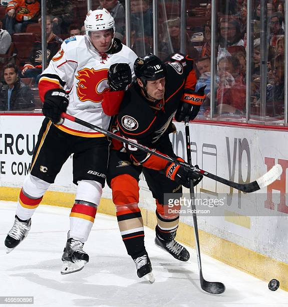 Sven Baertschi of the Calgary Flames battles Tim Jackman of the Anaheim Ducks for the puck on November 25 2014 at Honda Center in Anaheim California
