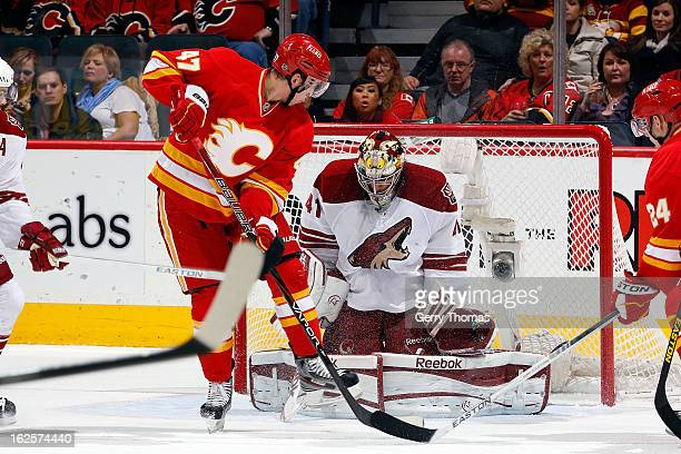 Sven Baertschi of the Calgary Flames skates in front of Mike Smith of the Phoenix Coyotes on February 24, 2013 at the Scotiabank Saddledome in...