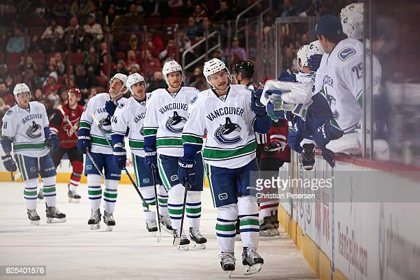 Sven Baertschi of the Vancouver Canucks celebrates with teammates on the bench after scoring a goal against the Arizona Coyotes during the first...