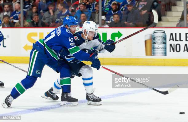 Sven Baertschi of the Vancouver Canucks checks Nikolaj Ehlers of the Winnipeg Jets during their NHL game at Rogers Arena October 12 2017 in Vancouver...
