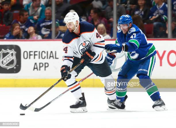 Sven Baertschi of the Vancouver Canucks checks Zack Kassian of the Edmonton Oilers during their NHL game at Rogers Arena October 7 2017 in Vancouver...