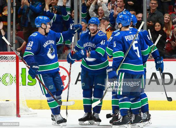 Sven Baertschi of the Vancouver Canucks is congratulated by teammates Bo Horvat and Derrick Pouliot after scoring his second goal during their NHL...