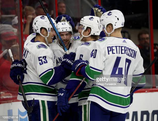 Sven Baertschi of the Vancouver Canucks scores a goal and is congratulated by teammates Bo Horvat and Elias Pettersson during an NHL game against the...