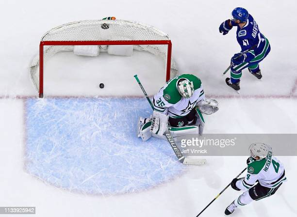 Sven Baertschi of the Vancouver Canucks scores on Anton Khudobin of the Dallas Stars during their NHL game at Rogers Arena March 30, 2019 in...