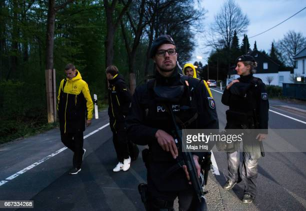 Sven Bender Marcel Schmelzer and Nuri Sahin of Borussia Dortmund are escorted to a car by police after the team bus of the Borussia Dortmund was...