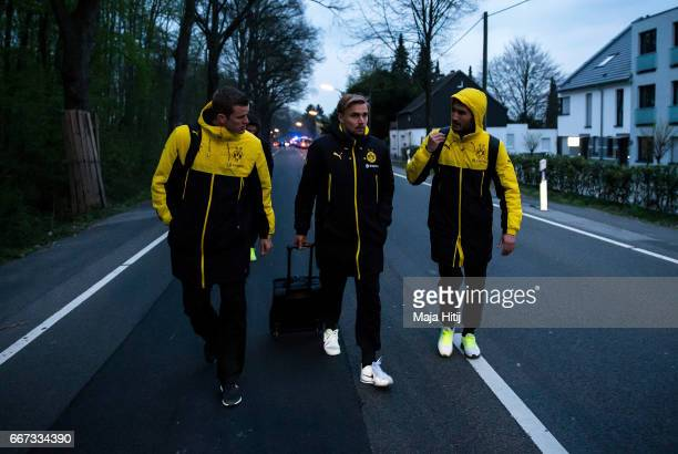 Sven Bender Marcel Schmelzer and Nuri Sahin of Borussia Dortmund walk to a car after the team bus of the Borussia Dortmund was damaged in an...