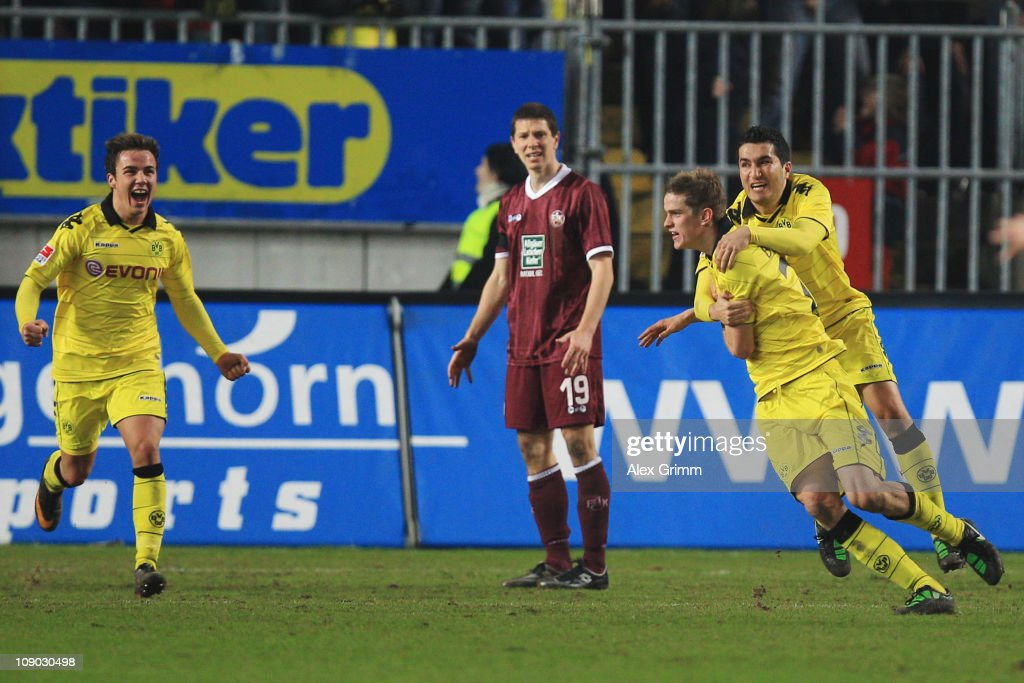 Sven Bender (2R) of Dortmund celebrates his team's first goal with team mates Nuri Sahin (R) and Mario Goetze (L) as Jiri Bilek (2L) of Kaiserslautern reacts during the Bundesliga match between 1. FC Kaiserslautern and Borussia Dortmund at Fritz-Walter-Stadion on February 12, 2011 in Kaiserslautern, Germany.