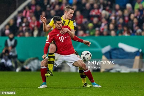 Sven Bender of Dortmund hinten and Robert Lewandowski of Bayern Munich battle for the ball during the German Cup semi final soccer match between FC...