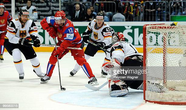 Sven Butenschoen , Dimitri Kotschnew and Christoph Ullmann of Germany battles for the puck with a player of Russia during the IIHF World Championship...