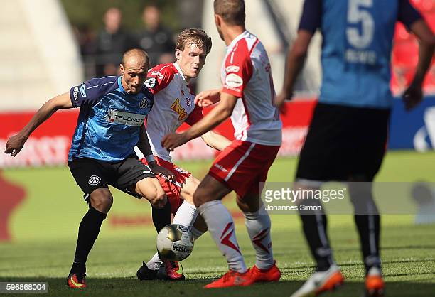 Sven Kopp and Marco Gruettner of Regensburg and Matthias Morys of Aalen fight for the ball during the the Third League match between Jahn Regensburg...