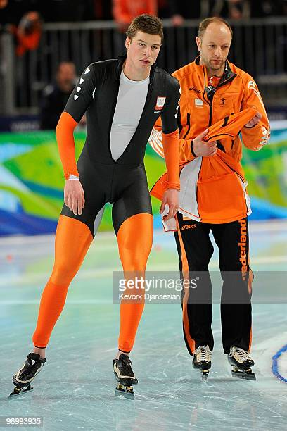 Sven Kramer of Netherlands reacts with coach Gerard Kemkers after finishing first but being disqualified in the men's speed skating 10000 m on day 12...