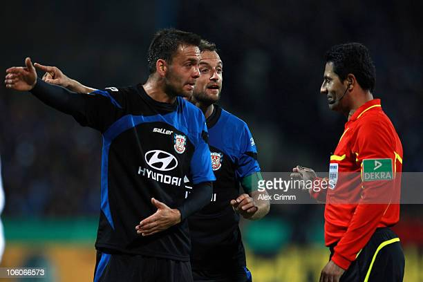 Sven Mueller and Bjoern Schlicke of Frankfurt argue with referee Babak Rafati during the DFB Cup second round match between FSV Frankfurt and FC...