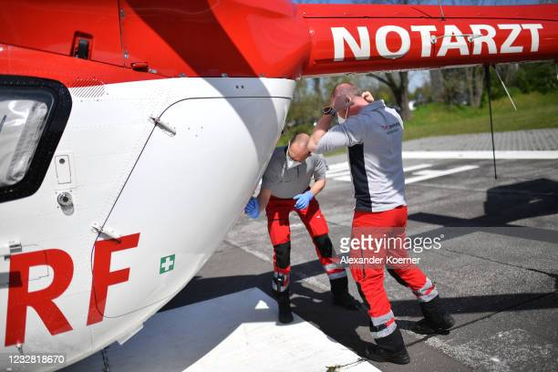 Sven Reinecke and emergency doctor Martin Fleiderer prepare to take a patient at AIRBUS H145 of DRF Luftrettung emergency air medical services at...
