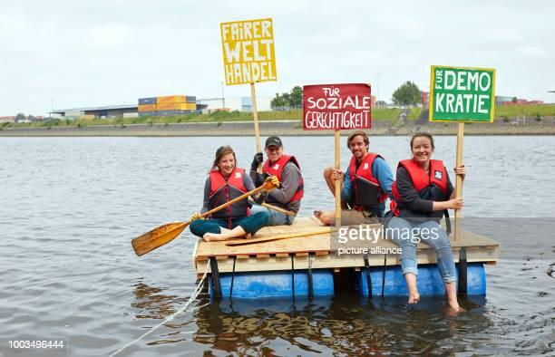 Svenja Angenendt Matthias Flieder Jonathan Krink und Greta Hausbeck test a raft built out ouf recycling materials and hold up banners reading 'Fairer...