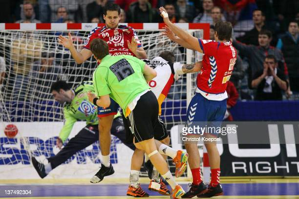 SvenSoeren Christophersen of Germany scores the decision goal to play a 2121 draw during the Men's European Handball Championship second round group...