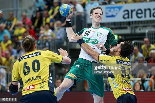 SvenSoeren Christophersen of Hannover is challenged by Alexander Petersson and Kim Ekdahl du Rietz of RheinNeckar Loewen during the DKB Handball...
