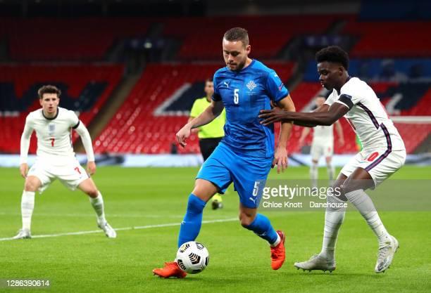 Sverrir Ingi Ingason of Iceland and Bukayo Saka of England in action during the UEFA Nations League group stage match between England and Iceland at...