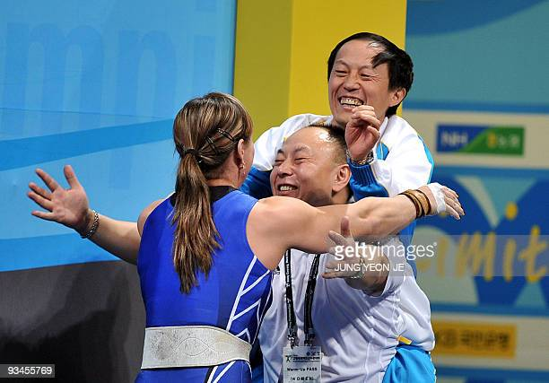 Svetiana Podobedova of Kazakhstan celebrates with her team members after setting a new world record in the snatch of the women's 75kg category event...