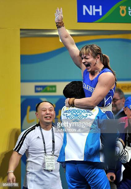 Svetiana Podobedova of Kazakhstan celebrates with her team members after setting a new world record in the clean and jerk of the women's 75kg...