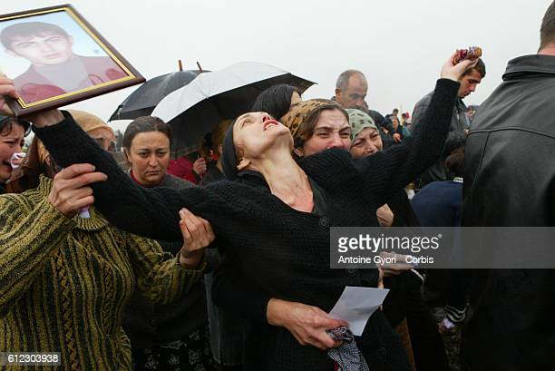 Svetlana Khoutsistova holds up a portrait of her son Azamat aged 26 who died in the Beslan school siege at Vladikavkaz cemetery surrounded by...