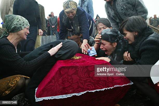 Svetlana Khoutsistova surrounded by mourners cries over the coffin of her son Azamat aged 26 who died in the Beslan school siege at Vladikavkaz...
