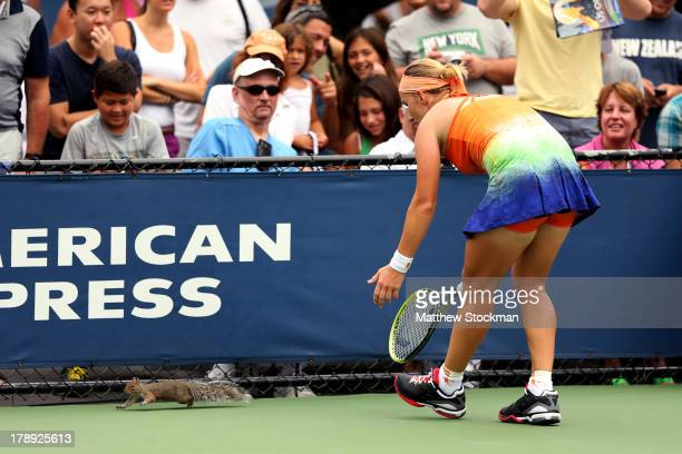 Svetlana Kuznetsova of Russia attempts to remove a squirrel from the court during her women's singles third round match against Flavia Pennetta of...