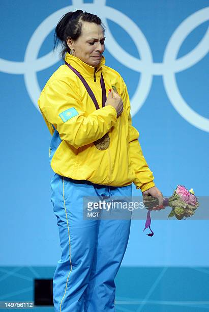 Svetlana Podobedova of Kazakhstan can't hold back the tears during the medals ceremony following her gold medal win in the women's 75kg weightlifting...