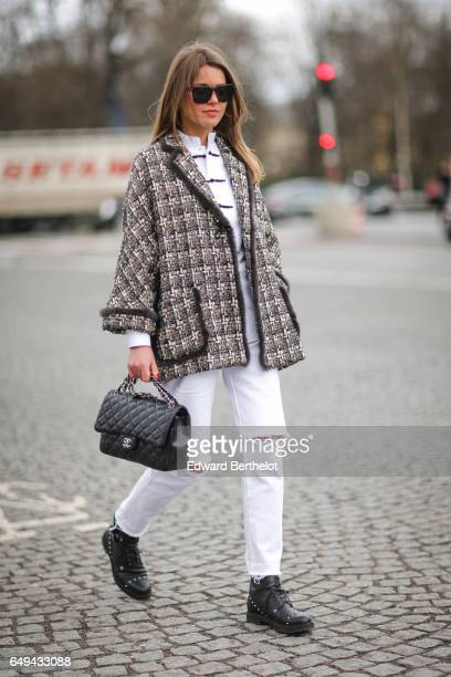 Svetlana Shashkova wears a tweed jacket a Chanel bag white ripped pants and black shoes outside the Chanel show during Paris Fashion Week Womenswear...