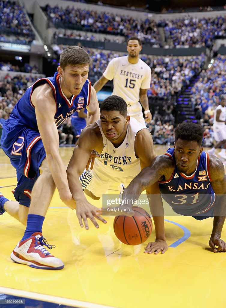 Sviatoslav Mykhailiuk #10 and Jamari Traylor #31 of the the Kansas Jayhawks and Karl-Anthony Towns #12 of the Kentucky Wildcats battle for a loose ball during the game against in the State Farm Champions Classic at Bankers Life Fieldhouse on November 18, 2014 in Indianapolis, Indiana.