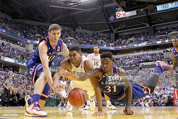 Sviatoslav Mykhailiuk and Jamari Traylor of the the Kansas Jayhwaks and Karl-Anthony Towns of the Kentucky Wildcats battle for a loose ball during...