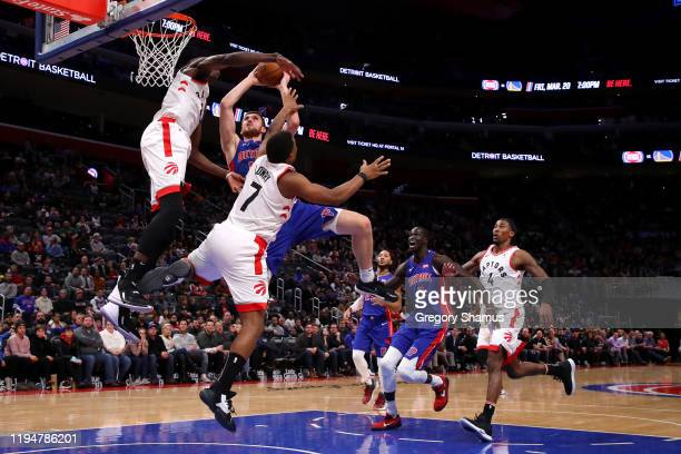 Sviatoslav Mykhailiuk of the Detroit Pistons drives to the basket against Chris Boucher and Kyle Lowry of the Toronto Raptors during the second half...