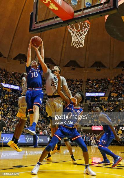 Sviatoslav Mykhailiuk of the Kansas Jayhawks and Esa Ahmad of the West Virginia Mountaineers battle for a rebound at the WVU Coliseum on January 15...