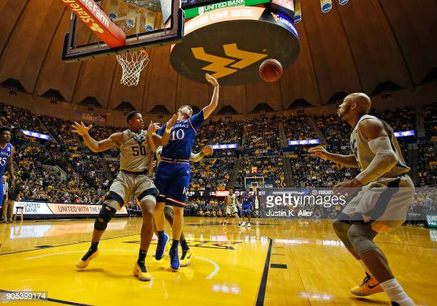 Sviatoslav Mykhailiuk of the Kansas Jayhawks and Sagaba Konate of the West Virginia Mountaineers battle for an inbound at the WVU Coliseum on January...