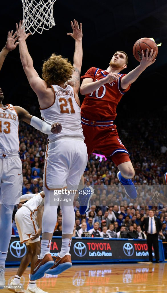 Sviatoslav Mykhailiuk #10 of the Kansas Jayhawks lays the ball up and around Dylan Osetkowski #21 of the Texas Longhorns in the first half at Allen Fieldhouse on February 26, 2018 in Lawrence, Kansas.