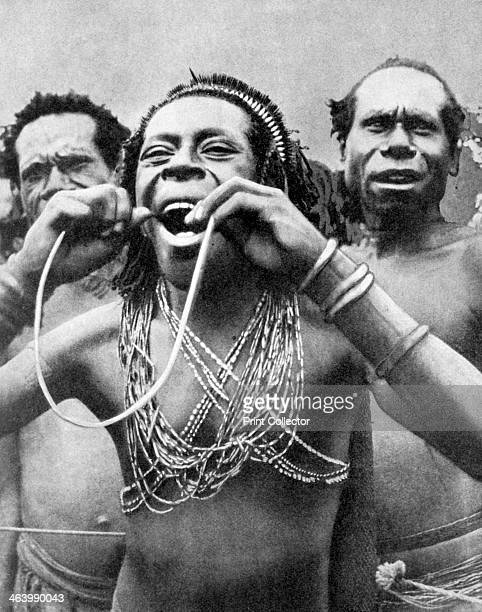 Swallowing canes in a ceremonial ritual New Guinea 1936 From Peoples of the World in Pictures edited by Harold Wheeler published by Odhams Press Ltd