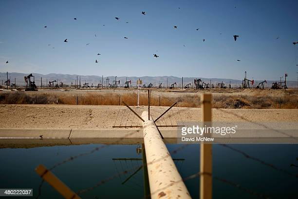 Swallows fly past a high pressure gas line crossing a canal in an oil field over the Monterey Shale formation where gas and oil extraction using...