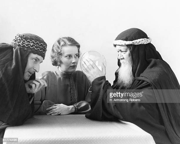 Swami looking into crystal ball, with woman and man watching intently.