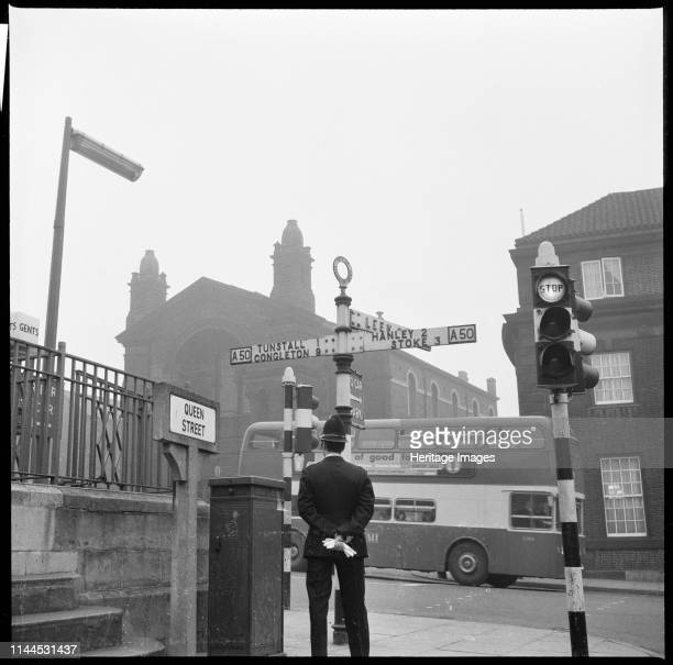 Swan Square, Burslem, Stoke-on-Trent, 1965-1968. A policeman standing beside a signpost at the junction of Queen Street and Swan Square with the...