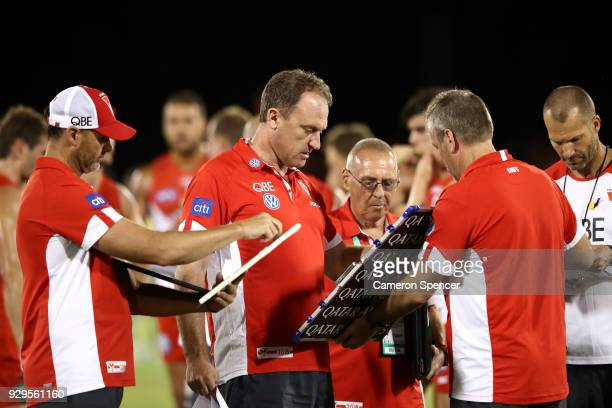 Swans head coach John Longmire talks to players a quarter time during the JLT Community Series AFL match between the Sydney Swans and the Greater...