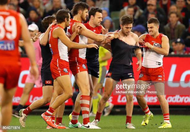 Swans players wrestle with Tomas Bugg of the Demons during the 2017 AFL round 15 match between the Melbourne Demons and the Sydney Swans at the...