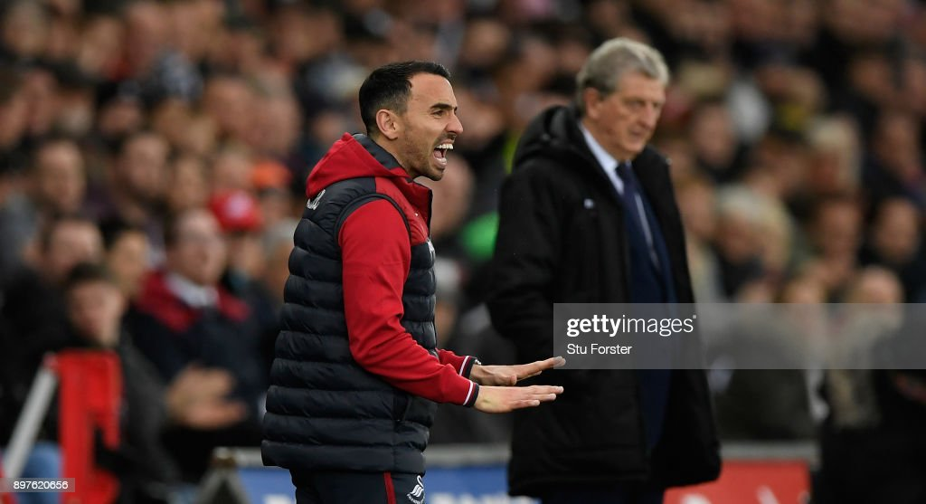 Swansea caretaker manager Leon Britton (l) reacts as Roy Hodgson looks on during the Premier League match between Swansea City and Crystal Palace at Liberty Stadium on December 23, 2017 in Swansea, Wales.