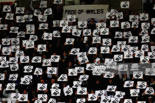 Swansea City fans hold up placards during the Barclays Premier League match between Swansea City and Cardiff City at the Liberty Stadium on February...