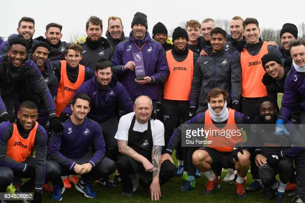 Swansea City manager Paul Clement with his Barclays Manager of the Month award and players and staff at Swansea City's training ground at Fairwood on...
